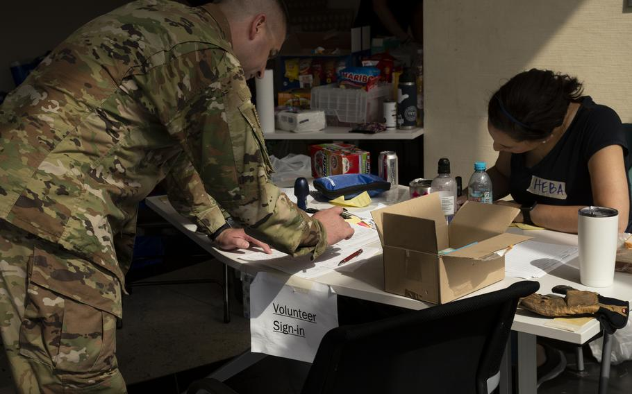 A military volunteer signs up to help with relief efforts for Afghan refugees at Ramstein Air Base on Aug. 26, 2021.
