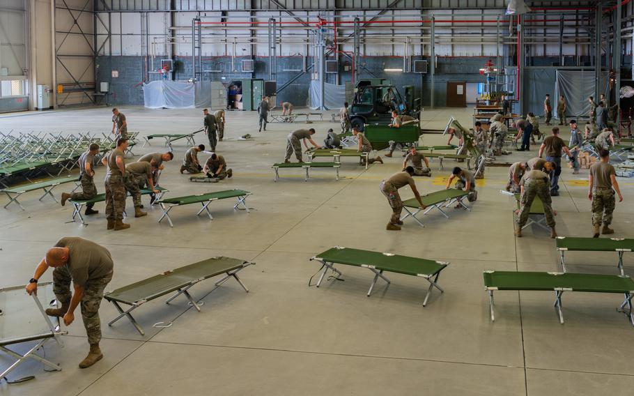 Airmen set up cots at a hangar on Ramstein Air Base, Germany, Aug. 19, 2021. Ramstein Air Base is providing lodging for evacuees from Afghanistan as part of Operation Allies Refuge during the next several weeks.