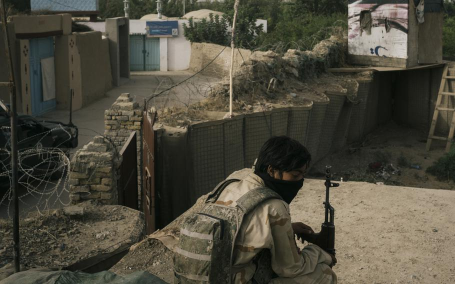 A police officer sits in an outpost in Kandahar, Afghanistan, as Afghan security forces find themselves engaged in a battle with the Taliban inside the city limits.