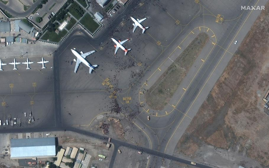 This satellite photo from Maxar Technologies shows swarms of people on the tarmac at Kabul International Airport on Monday Aug. 16, 2021.