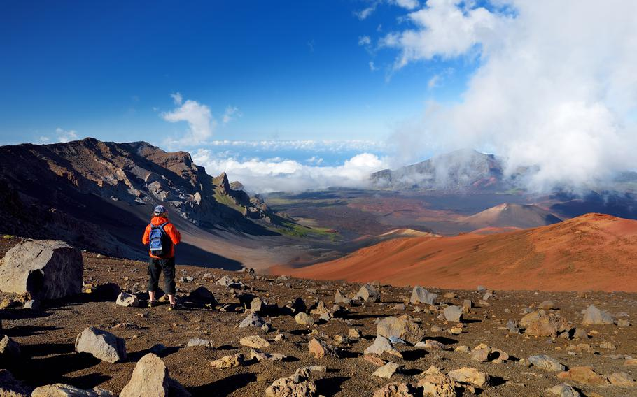 A hiker stands at the edge of the Haleakala crater. According to one of the many legends associated with the Polynesian demigod Maui, he captured the sun at the 10,000-foot summit of Haleakala. After receiving a promise from the sun to traverse the sky more slowly, so people would have more daylight, Maui released his captive. The mythology of a place greatly influences the everyday lives of locals. Understanding that mythology is akin to speaking the local language beyond the ability to order off a menu.