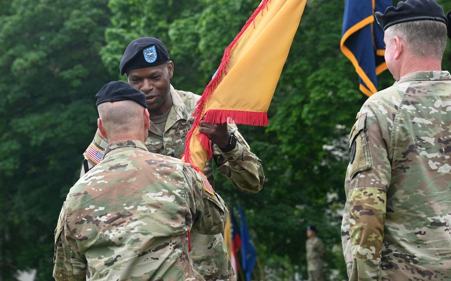 Brig. Gen. James Smith, the incoming leader of the 21st Theater Sustainment Command, takes the unit colors from U.S. Army Europe and Africa commander Gen. Christopher Cavoli at the 21st TSCs change of command ceremony at Daenner Kaserne, Kaiserslautern, Germany, June 8, 2021. At right is the outgoing commander, Maj. Gen. Christopher Mohan.