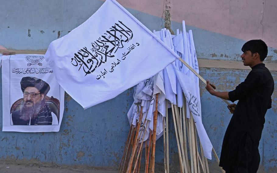 A vendor holds a Taliban flag next to a poster of Taliban leader Mullah Abdul Ghani Baradar as he waits for customers along a street in Kabul on August 27, 2021, following the Taliban's military takeover of Afghanistan.