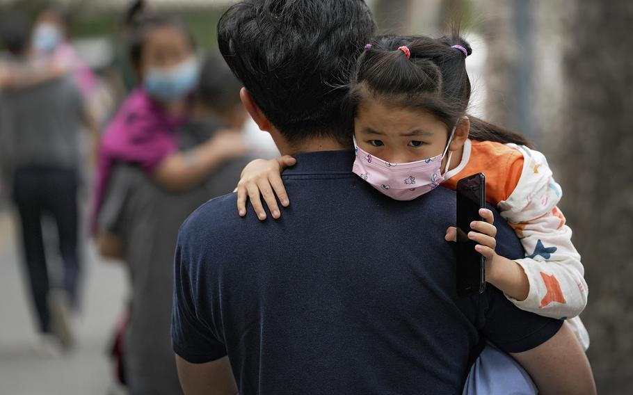 A child is carried to a kindergarten in Beijing on June 9, 2021. If China is to meet its tentative goal of vaccinating 80% of its population against the coronavirus by the end of the year, tens of millions of children may have to start rolling up their sleeves.