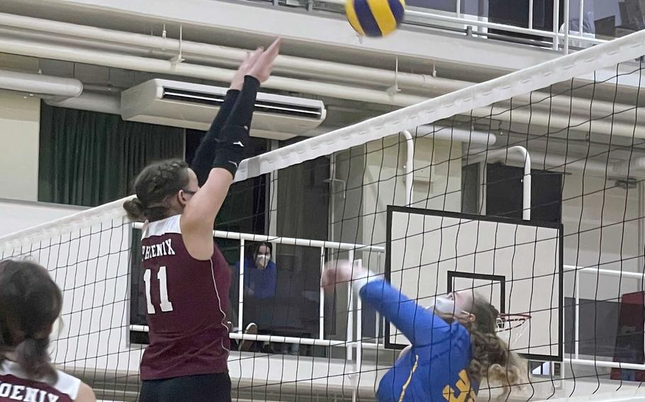 Yokota's Devynn Martin bumps the ball at the net as Seisen's Ariana Hill looks to block during Wednesday's Kanto Plain volleyball match. The Phoenix won in straight sets.