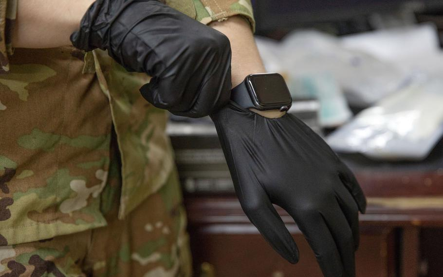 Army Sgt. Kayla Sampson pulls on a medical glove while training at Camp Buehring, Kuwait, July 30, 2020.