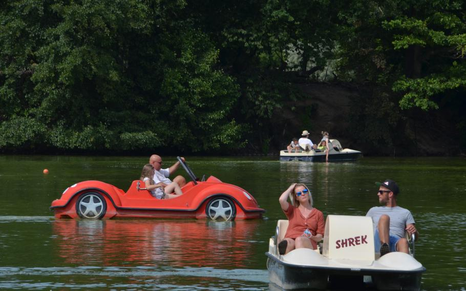 People ride in paddle boats on the lake in the Kurpark in Bad Nauheim, Germany, Aug. 15, 2021. The lake, the park and paddle boats are some of the attractions of the spa town, where Elvis Presley lived from 1958-1960.