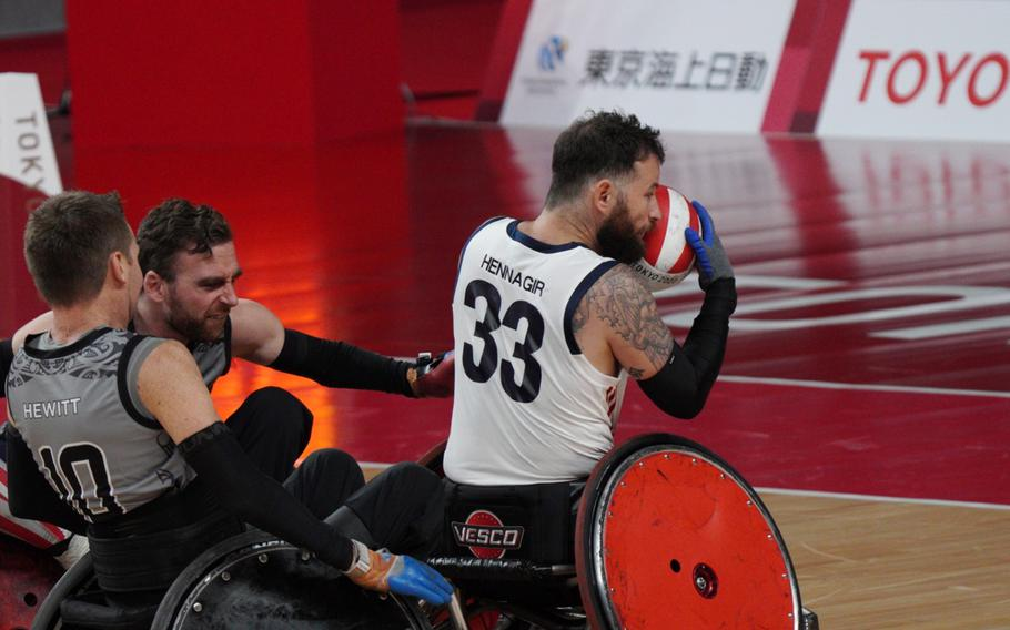 Former Marine Raymond Hennagir grabs the ball in Team USA's wheelchair rugby win over New Zealand during the Tokyo Paralympics, Wednesday, Aug. 25, 2021.