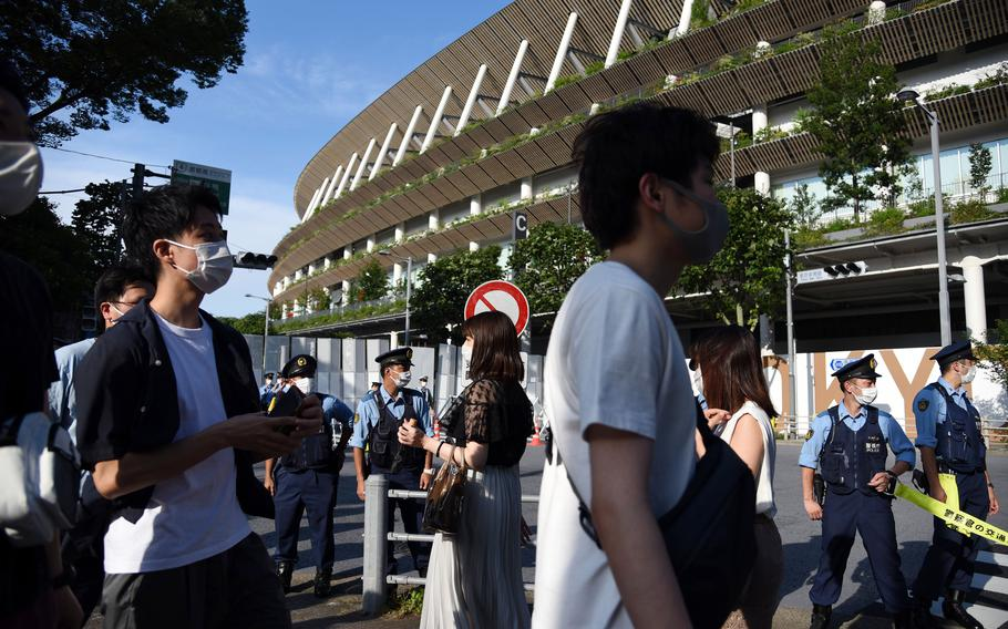 People in masks gawk at the new National Stadium hours before the opening ceremony for the pandemic-delayed Tokyo Olympics, Friday, June 23, 2021.