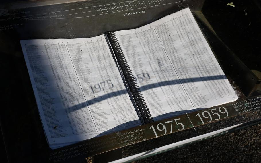 The sun casts a shadow on a book containing information on the location of names on the Vietnam wall, May 31, 2021.