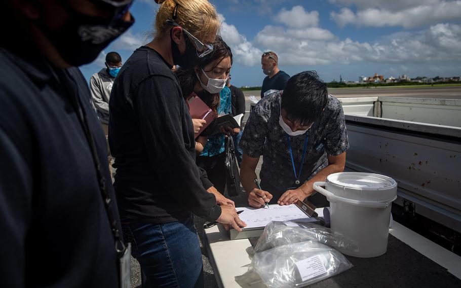 Japanese officials collect samples of treated wastewater at Marine Corps Air Station Futenma, Okinawa, July 19, 2021.
