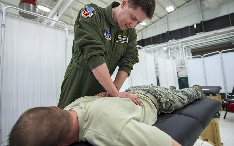 Air Force Maj. Matthew Puderbaugh, of the 133rd Medical Group, performs a musculoskeletal adjustment on an airman in St. Paul, Minn., in 2019. Between 31% and 44% of active-duty service members deal with chronic pain, the nonpartisan Rand Corp. said in a recent study, adding that back pain and joint disorders are the most common types of chronic pain experienced by troops.