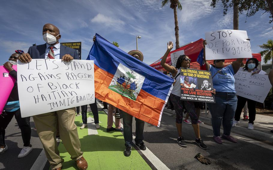 Protestors chant slogans in front of the USCIS district office in Miami as members of Miami's Haitian community protest Sept. 22, 2021 against the Biden administration for their handling of Haitian immigrants at the U.S.-Mexico border.