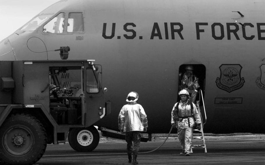 Taszar AB, Hungary, January, 1996: Firefighters inspect an Air Force cargo plane after a fire ignited from a car battery during offloading procedures.
