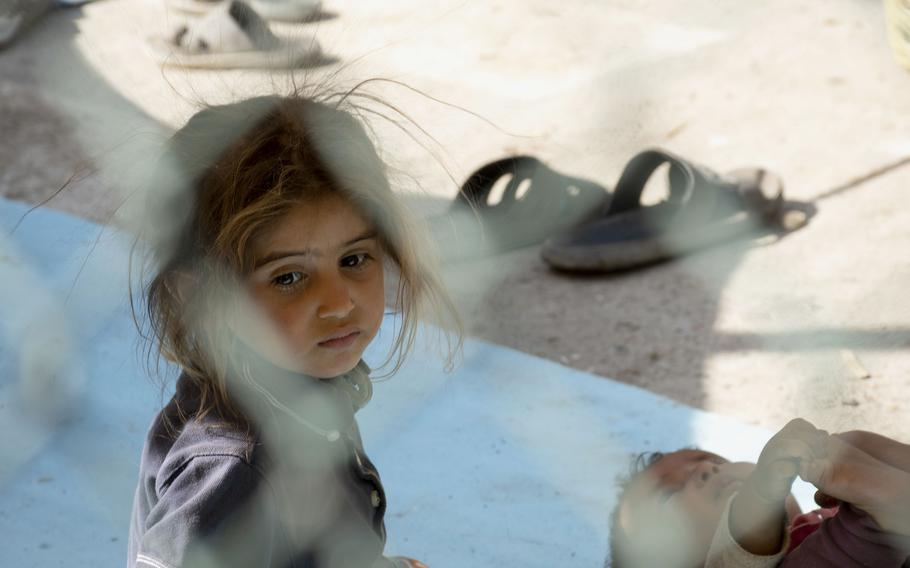 A young girl forced to flee her home following a Taliban advance sits at a park in Afghanistan on Friday, Aug. 13, 2021.