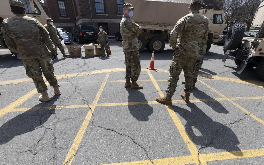 Massachusetts National Guard soldiers help with logistics in this April 17, 2020 file photo, at a food distribution site outside City Hall, in Chelsea, Mass. Gov. Charlie Baker on Monday, Sept. 13, 2021, activated the state's National Guard to help with busing students to school as districts across the country struggle to hire enough drivers.