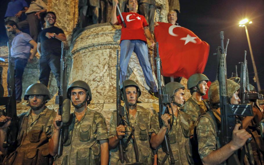 Turkish soldiers secure the area as supporters of Turkey's President Recep Tayyip Erdogan protest in Istanbul's Taksim square, early Saturday, July 16, 2016.