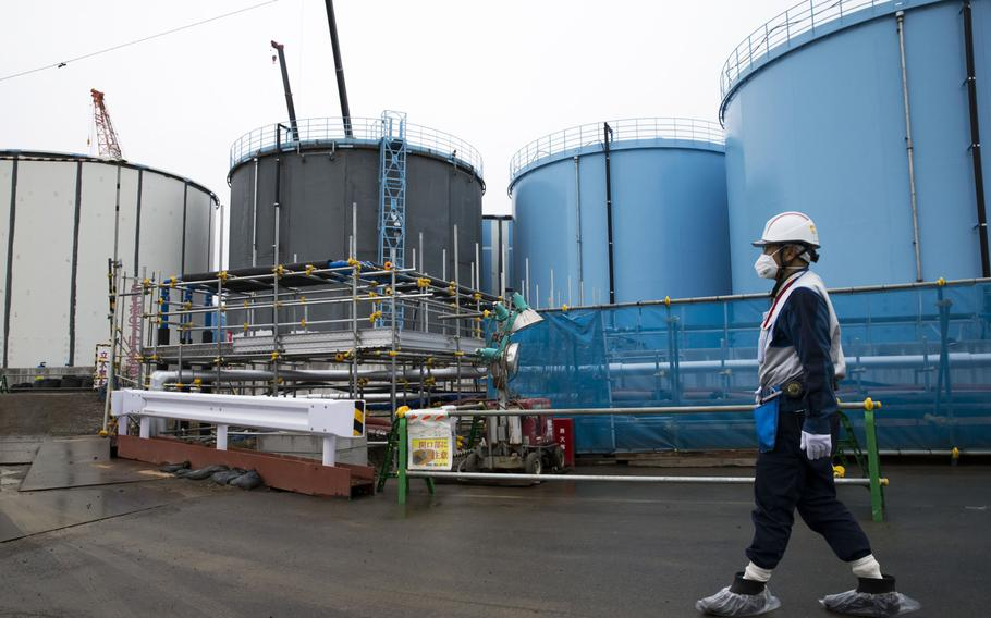 An employee walks past storage tanks for contaminated water at Tokyo Electric Power Co.'s Fukushima Dai-ichi nuclear power plant in Okuma, Japan, on Feb. 23, 2017.