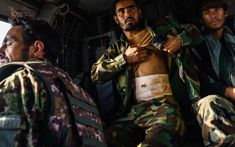 Soldiers, some wounded by Taliban gunfire, leave the Shah Wali Kot outpost in Kandahar, Afghanistan, aboard an UH-60 Blackhawk.