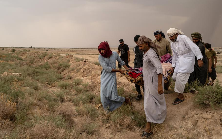 Relatives of Warda Obeid, a 60-year-old grandmother from Iraq's Anbar province, carry her body to a cemetery near al-Hol camp. Her nephew Saken Obeid, at right, in white, said she had died of a heart condition for which adequate treatment at the camp was unavailable.