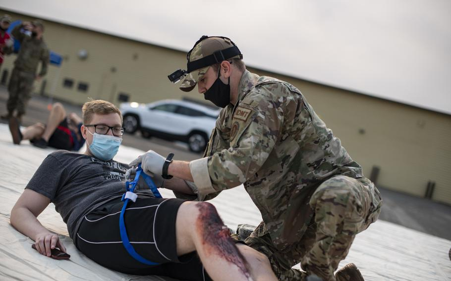 Staff Sgt. Casey Mulcahy, 9th Operational Medical Readiness Squadron operational medicine independent duty medical technician, tourniquets  a patient's simulated leg wound during exercise Ready Eagle, Aug. 6, 2021, at Beale Air Force Base, Calif. As one of the first responders to the scene, Mulcahy was responsible for the initial treatment and triaging of patients.