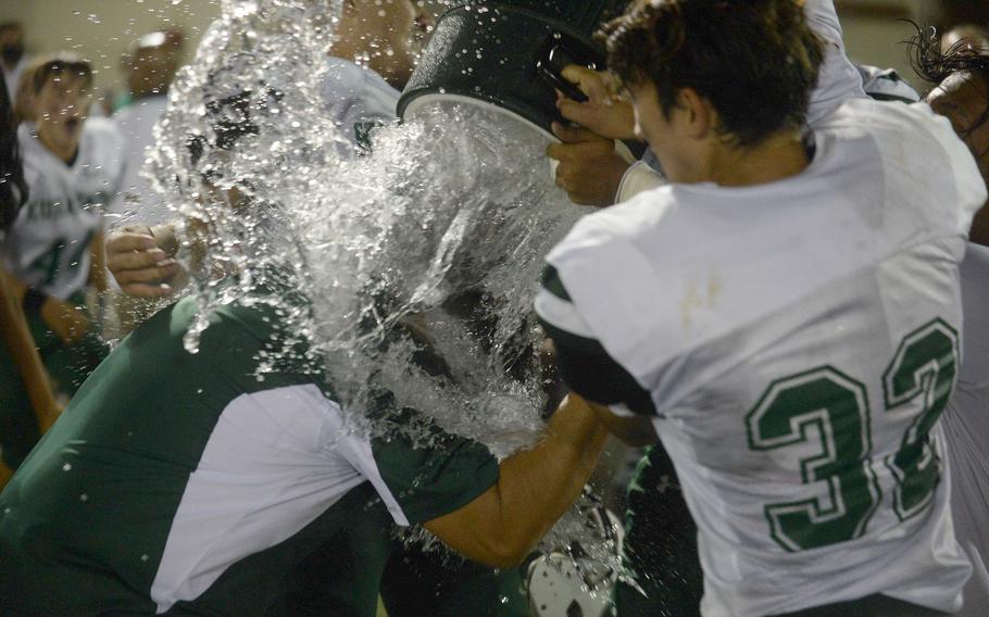 Kubasaki coach Tony Alvarado gets the water-bucket celebration treatment from his Dragons players.