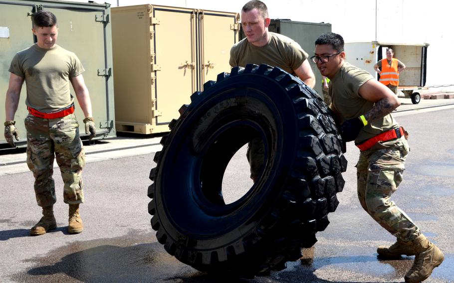 Staff Sgt. Matthew Rothrock and Senior Airman Gerald Dinio (right) flip a tire during the endurance event at the 721st Aerial Port Squadron Multi-Capable Airmen Rodeo at Ramstein Air Base, July 23, 2021. The tire the pair from Spangdahlem Air Base had to move was filled with water.