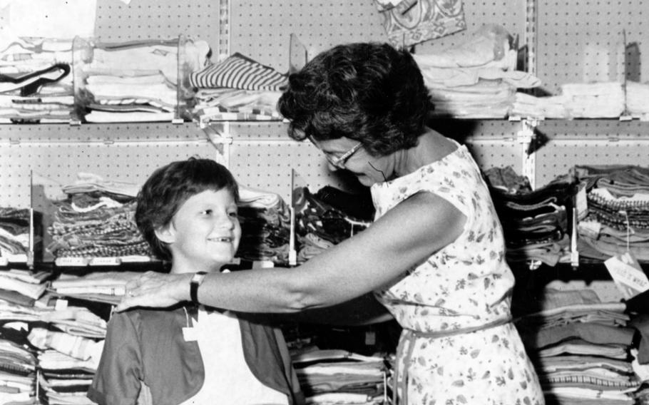 Youngsters stock up with school supplies and back-to-school clothes at the Naha Air Base Exchange as they prepare for the opening of U.S. dependent schools on Okinawa. Stacey Somppi's mom makes sure she has a proper fit for her new back-to-school dress on Aug. 25, 1962.