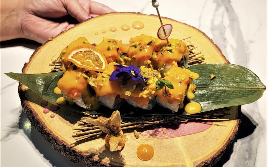 The uramaki mango roll has salmon and avocado inside. On the outside, it has salmon, cream of mango, flying fish roe, minced pistachio and a basil sauce.