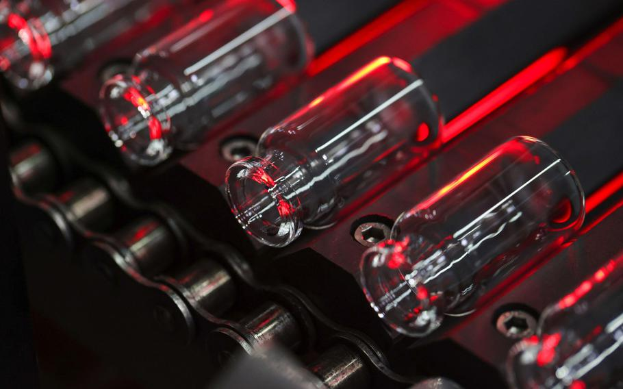 Glass vials move along a conveyor at the Gerresheimer medical glassware factory in Buende, Germany, on Aug. 11, 2020.