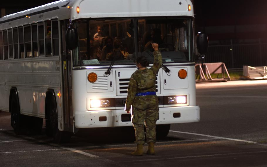 An airman directs a bus carrying evacuees from Afghanistan at Ramstein Air Base, Germany, on Friday, Aug. 20, 2021. Hundreds of evacuees began arriving Friday from Al Udeid Air Base, Qatar, after fleeing the Taliban.