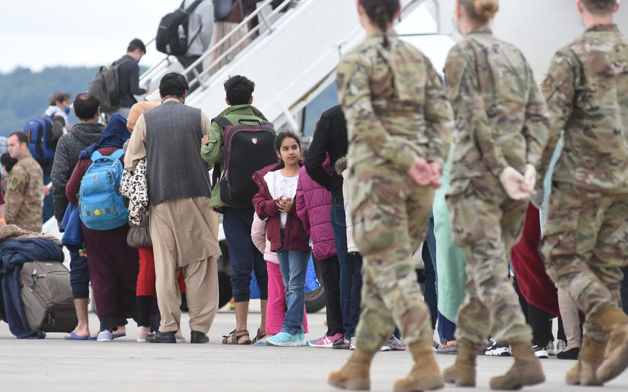 Evacuees from Afghanistan board a commercial flight going to the United States on Aug. 26, 2021, after a temporary stay at Ramstein Air Base, Germany. Health officials administered more than 12 measles, mumps and rubella vaccinations Thursday ahead of mass vaccinations scheduled to begin Friday at Ramstein and nearby Rhine Ordnance Barracks.
