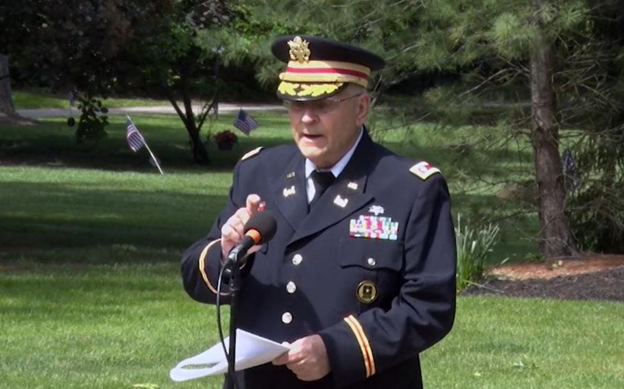 In this image captured from Hudson public access television, retired Army Lt. Col. Barnard Kemter checks to see if the microphone is functioning after organizers turned off audio during a portion of his Memorial Day speech Monday, May 31, in Hudson, Ohio.