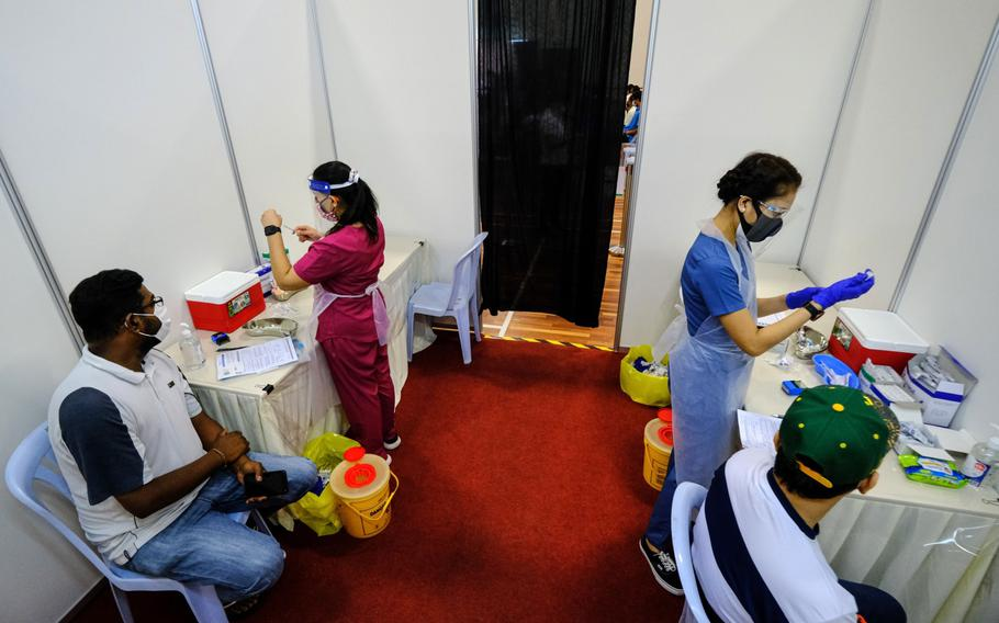 Health workers prepare doses of Covid-19 vaccine for sailors and port workers in Port Klang, Malaysia, on June 25.