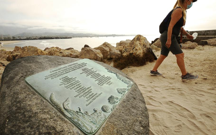 On the first anniversary of the 2019 Conception boat fire, Susan Tibbles walks past a memorial for the 34 people who died, in Santa Barbara, Calif.