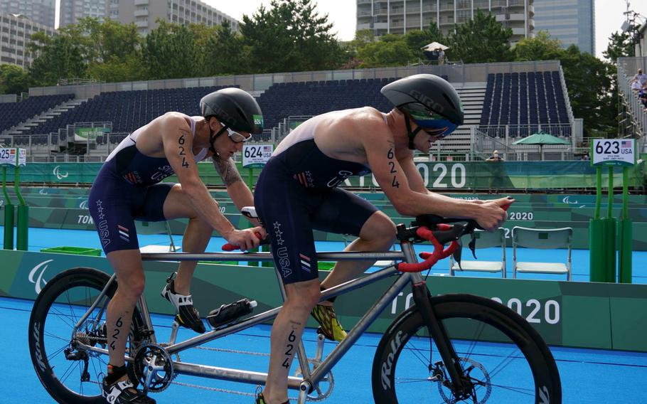 Team USA's Bradley Snyder, left, and Greg Billington ride a tandem bike on their way to Paralympic triathlon gold at Odaiba Marine Park in Tokyo, Saturday, Aug. 28, 2021. Snyder is a Navy veteran who lost his sight from a blast in Afghanistan in 2011.