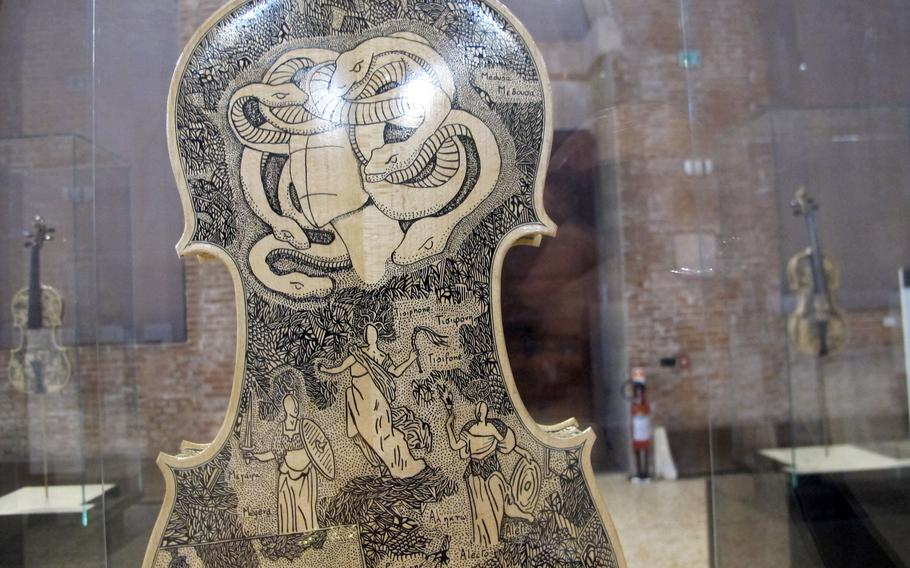 Snakes in hell are shown on one of 33 violins painted with scenes from the great medieval Italian poet Dante's Divine Comedy. The exhibit is at the Palladian Basilica in Vicenza, Italy through Aug. 31.