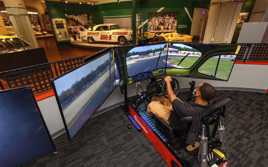 """In this image provided by the The Henry Ford, a person tries the auto racing simulator, part of the Driven To Win exhibit at the The Henry Ford Museum in Dearborn, Mich. The """"Driven to Win"""" exhibit took more than a decade from concept to its opening earlier this year."""