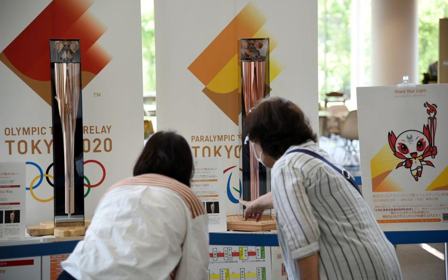 People check out torches for the Tokyo Olympic and Paralymic games on display at Chigasaki City Hall in Kanagawa prefecture, Japan, Tuesday, June 8, 2021.
