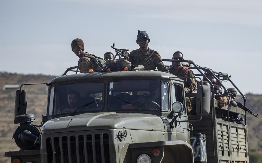 Ethiopian government soldiers ride in the back of a truck on a road near Agula, in the Tigray region of northern Ethiopia, on May 8, 2021. As the Tigray People's Liberation Front and the government forces fight, civilians, and especially children, are suffering heavily.