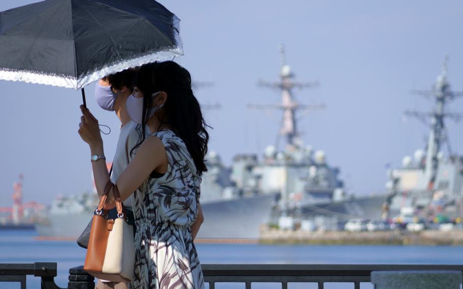A couple strolls past ships moored at Yokosuka Naval Base, Japan, Friday, Sept. 24, 2021.