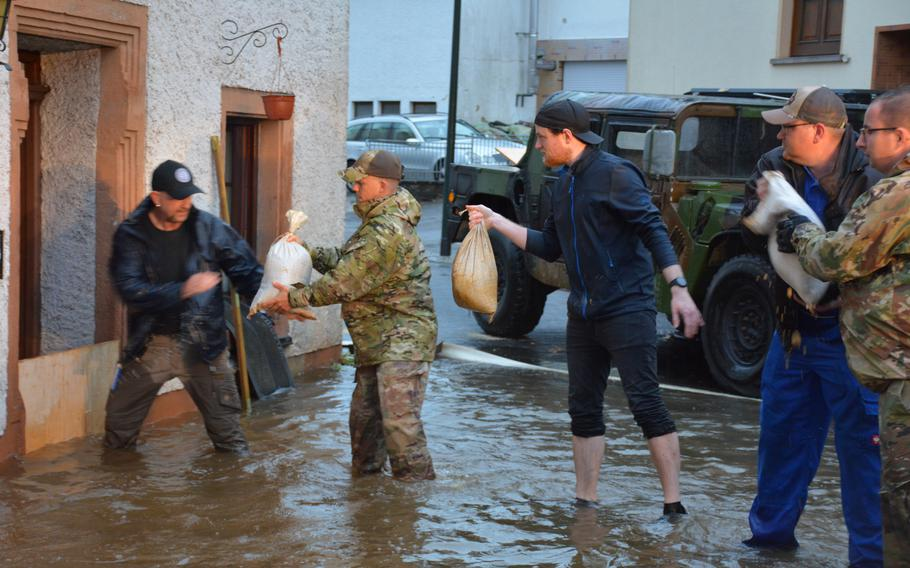 Members of Spangdahlem Air Base's 52nd Civil Engineering Squadron pass along sandbags with German first responders to prevent flooding in Binsfeld, Germany, July 14, 2021.