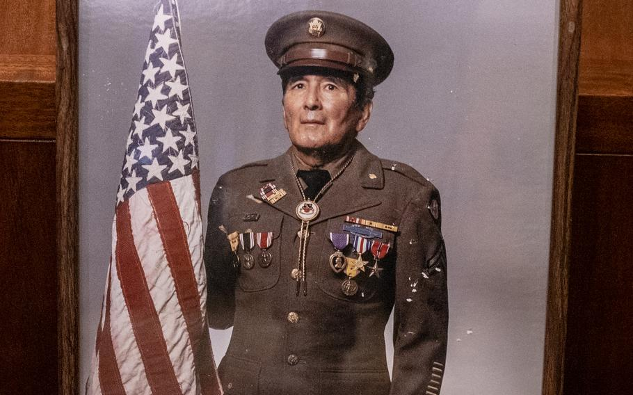 """In this photo, Joseph O. """"Jose"""" Quintero wears his U.S. Army uniform and holds the American flag he made while being held in a Japanese prisoner of war camp."""