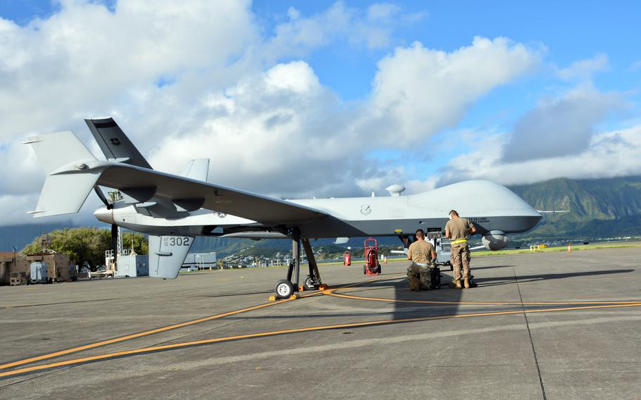 Technicians prepare an Air Force MQ-9 Reaper drone just before take-off at Marine Corps Base Hawaii, Monday, Sept. 27, 2021.