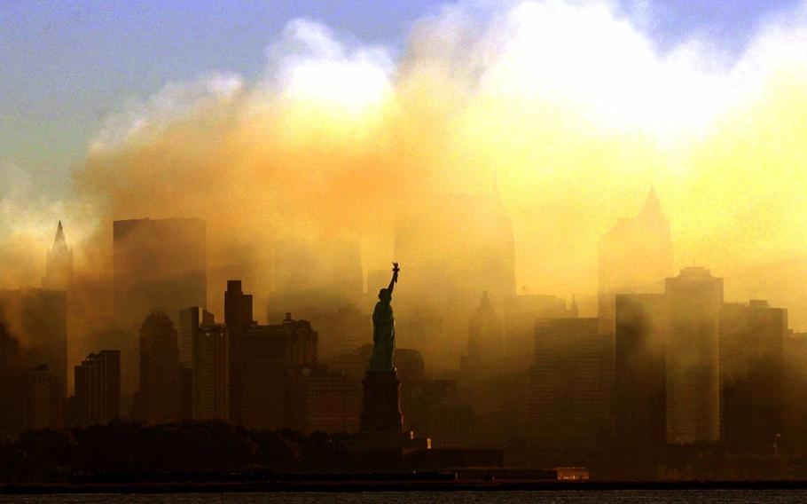 The Statue of Liberty stands in front of a smoldering lower Manhattan at dawn, seen from Jersey City, N.J., on Sept. 15, 2001 . The Sept. 11, 2001 terrorist attacks on the United States nearly 20 years ago precipitated profound changes in America and the world.