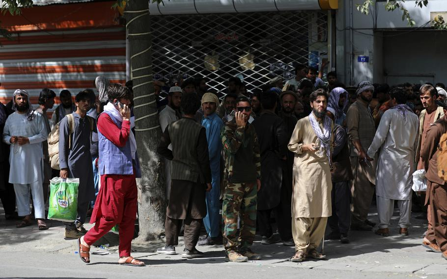 Afghans wait in long lines for hours to withdraw money, near Kabul Bank, in Kabul, Afghanistan, Sunday, Aug. 15, 2021.