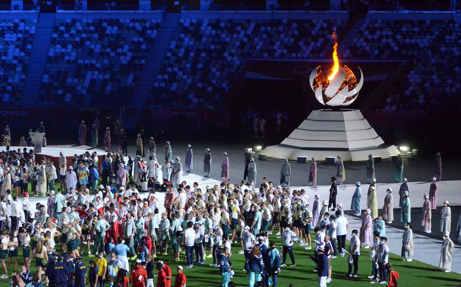 Athletes assemble near the Olympic flame during the closing ceremony of the Tokyo games, Sunday, Aug. 8, 2021.