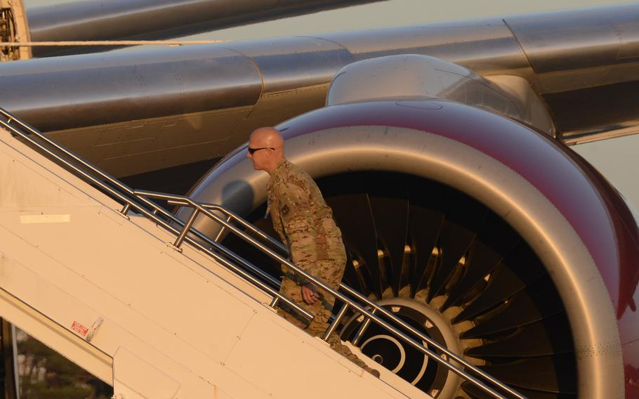 Brig. Gen. Josh Olson, commander of the 86th Airlift Wing, climbs stairs toward an Omni Air International Boeing 777 that was set to carry some 300 Afghans to the U.S. from Ramstein, Saturday, Oct. 9, 2021. The flight was the first to take Afghan refugees from Ramstein to the U.S. in around three weeks.