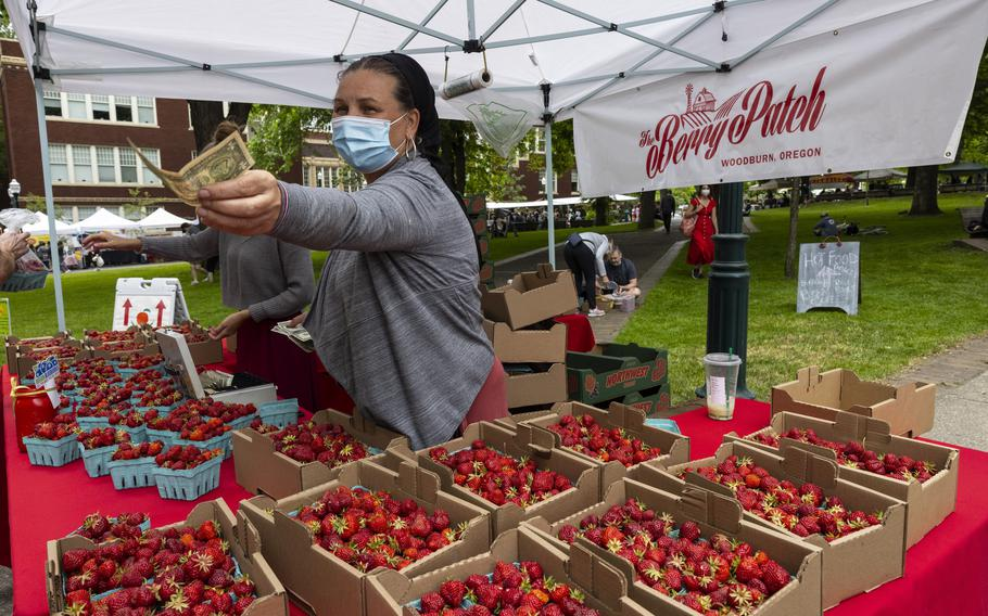 FILE - Nancy Sharabarin hands money to a customer buying strawberries at a farmers market in Portland, Ore., on June 5, 2021.  As the country opens up, and as summer kicks into high gear, farmers' markets are in full swing in many regions. An excursion to one of them is a fun and easy way to make the most out of a free morning with kids. (AP Photo/Paula Bronstein, File)