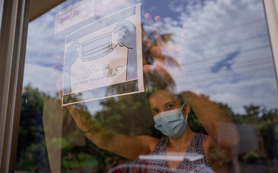A clothing store worker poses next to a sign encouraging the use of a masks during the COVID-19 pandemic at the entrance to the store in Managua, Nicaragua, Thursday, Sept. 9, 2021.